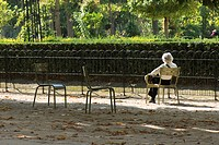 France, Paris, woman sitting alone in park, rear view