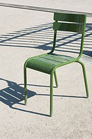 Green metal chair on gravel