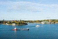 Sweden, Stockholm, Lake Malaren, tugboat pushing barge, city in background