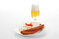 Sausages served with potato salad and cucumber in front of a glass of beer