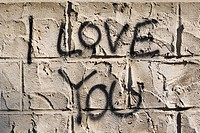 The words I love you as graffiti on the outside walls of a house