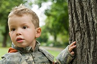 Four-year-old boy touching the tree bark in the park