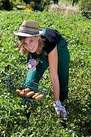 Young woman harvesting potatoes