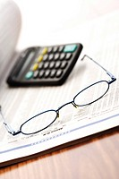 Pair of glasses on top of stock quotations with calculator, symbolic picture