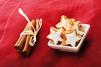 Cinnammon star-shaped biscuits and bundle of cinnammon sticks on red velvet