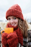 Female teenager wearing a hat and a scarf holding a tea cup