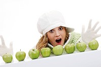 Young woman wearing a scarf and a cap, behind a row of green apples