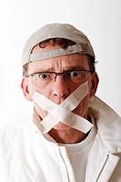 Painter with adhesive tape over his mouth