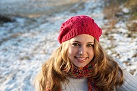 Laughing teenage girl wearing a hat and gloves, sitting in a wintery landscape