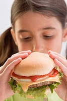 Little girl eating cheeseburger