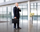 A mature businessman standing in modern office building, holding a briefcase