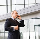 A mature businessman talking on mobile phone in modern office building