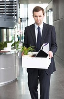 A redundant businessman taking his belongings home in a box