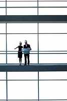 Two architects or developers standing on a walkway of an office building, looking at plans