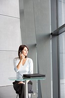 A businesswoman sitting at a glass table, talking on a mobile phone