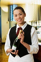 Hispanic waitress holding bottle of champagne