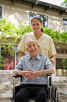 Senior Hispanic man outdoors in wheelchair with aide