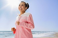 Hispanic woman jogging on beach