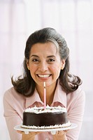 Hispanic woman holding birthday cake