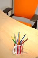 still life of office desk and chair with pencils in cup