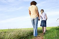 young mother and daughter walking hand in hand on path in the countryside