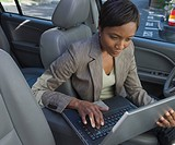 African businesswoman typing on laptop in car