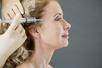 A middle_aged woman receiving a botox injection