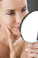 A middle_aged woman looking at her face in the mirror