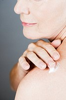 A senior woman applying moisturising cream to her shoulder