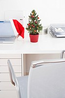 still life of little christmas tree and santa claus hat on office desk
