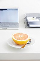 still life of grapefruit on plate on office desk