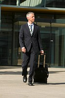 full body portrait of mature businessman with carry_on suitcase