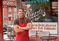 Mixed race business owner in apron in front of deli
