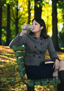 Mixed race woman drinking water on park bench in autumn