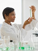 African scientist looking at vial of liquid