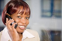 portrait of black businesswoman in front of window talking on mobile phone