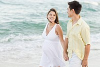 Husband holding hands with pregnant wife on beach