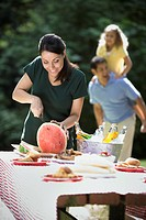 Hispanic family having picnic outdoors