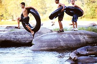 Three boys with inner tubes jumping into water