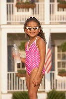 African girl in bathing suit holding water bottle