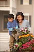 Asian mother and son watering flowers