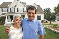 Portrait of Hispanic couple in front of house
