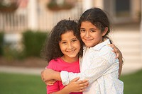 Portrait of Hispanic sisters hugging