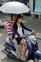 pretty Thai gal and friend on a motorbike in Bangkok Thailand