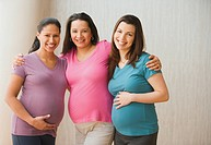 Three pregnant Hispanic women hugging and smiling