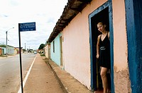 A Brazilian beauty stands at the door of a local bar