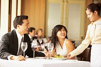 Waitress serving Asian couple at restaurant