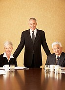 Three senior businesspeople at conference table