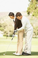 Man helping wife with golf swing
