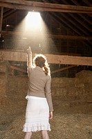 Rear view of Hispanic woman pointing at sunlight in barn
